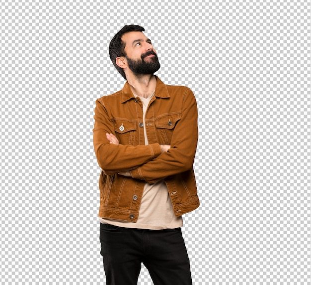 Homem bonito, com barba, olhando para cima, enquanto sorrindo