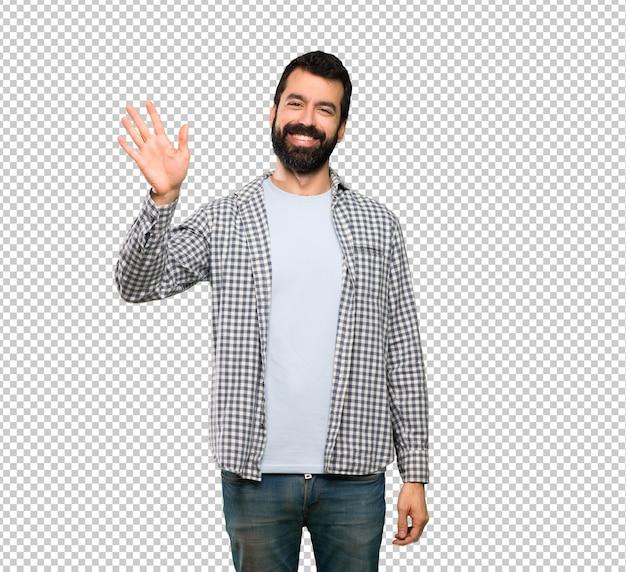 Homem bonito com barba saudando com a mão com expressão feliz