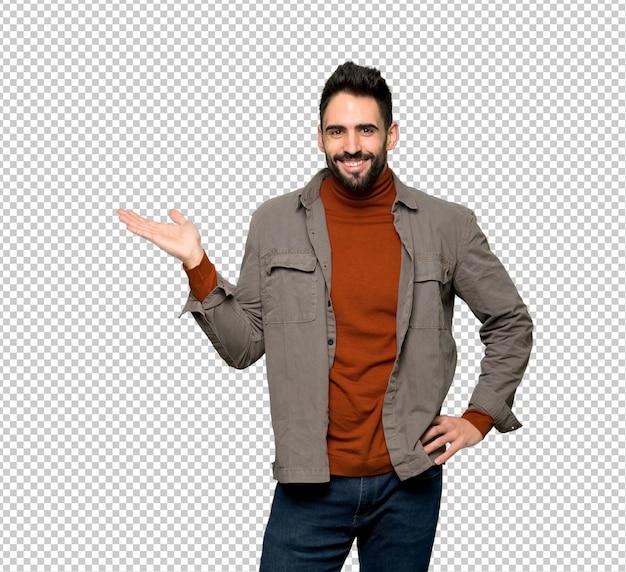 Homem bonito com barba segurando copyspace imaginário na palma da mão para inserir um anúncio