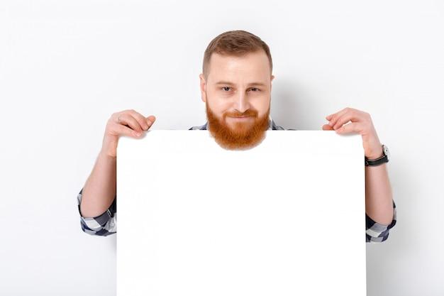 Homem bonito com barba segurando o cartão branco grande.