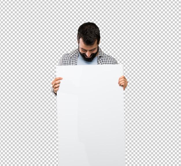 Homem bonito com barba segurando um cartaz vazio