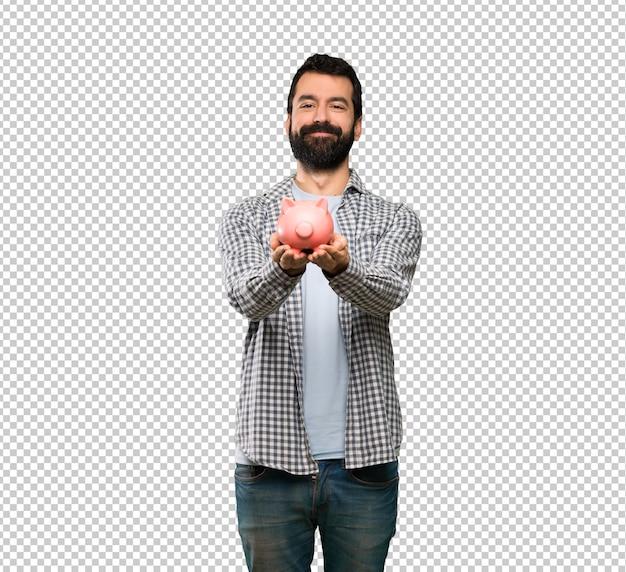 Homem bonito com barba segurando um piggybank