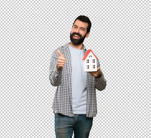 Homem bonito com barba segurando uma pequena casa