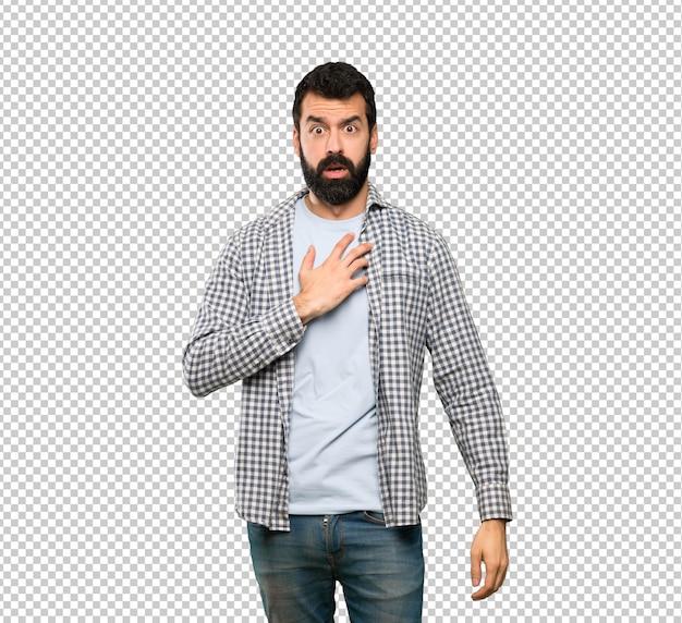 Homem bonito com barba surpreso e chocado enquanto olha para a direita