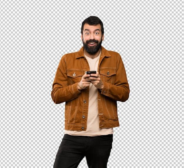 Homem bonito com barba surpreso e enviando uma mensagem