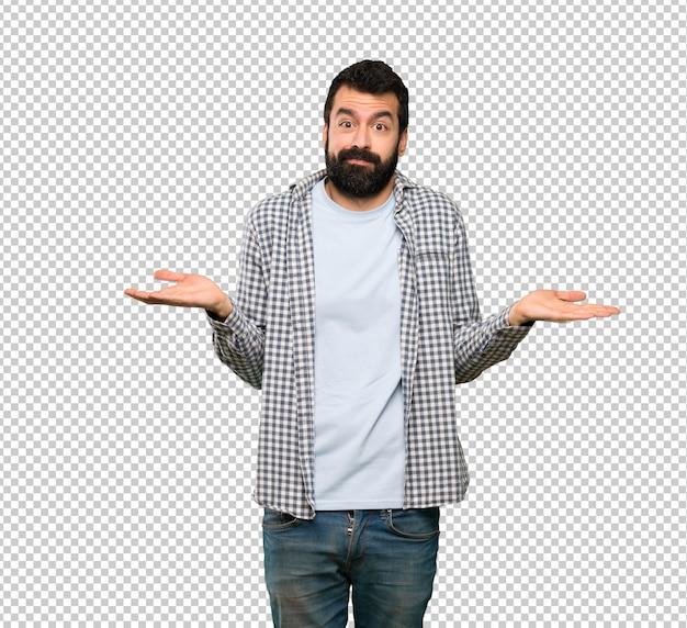 Homem bonito com barba tendo dúvidas ao levantar as mãos