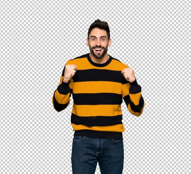 Homem bonito com blusa listrada comemorando uma vitória na posição de vencedor