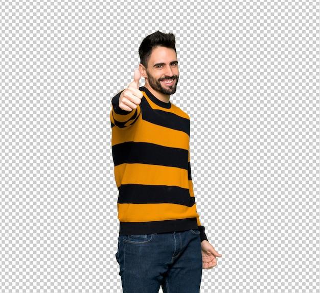 Homem bonito com blusa listrada dando um polegar para cima gesto porque algo bom aconteceu