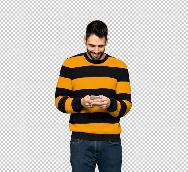 Homem bonito com blusa listrada, enviando uma mensagem com o celular