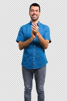 Homem bonito com camisa azul aplaudindo