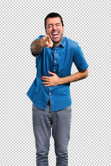 Homem bonito com camisa azul apontando com o dedo para alguém e rindo muito