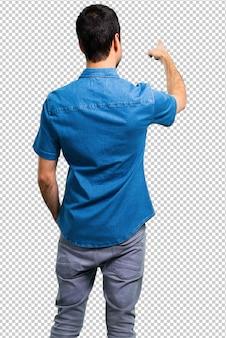 Homem bonito com camisa azul apontando para trás com o dedo indicador