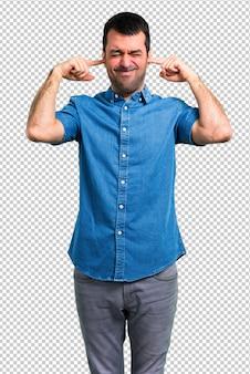 Homem bonito com camisa azul, cobrindo ambas as orelhas com as mãos