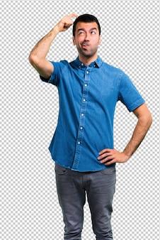 Homem bonito com camisa azul com dúvidas e com expressão de rosto confuso