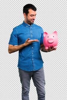 Homem bonito com camisa azul, segurando um piggybank