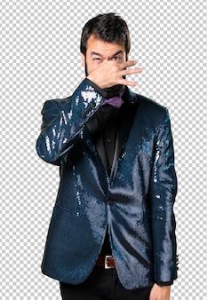 Homem bonito com casaco de lantejoulas fazendo cheiro mau gesto