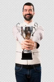 Homem bonito com colete segurando um troféu