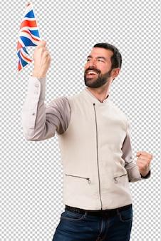 Homem bonito com colete segurando uma bandeira do reino unido
