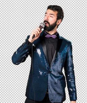 Homem bonito com jaqueta de lantejoulas cantando com microfone