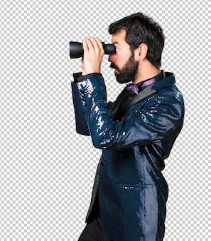 Homem bonito com jaqueta de lantejoulas com binóculos