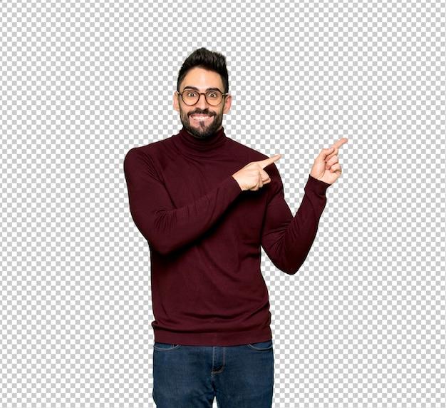 Homem bonito com óculos assustado e apontando para o lado