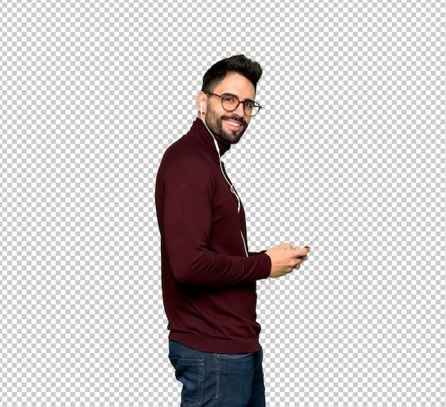 Homem bonito com óculos, enviando uma mensagem com o celular