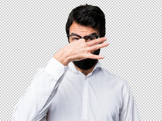 Homem bonito com óculos fazendo cheiro mau gesto