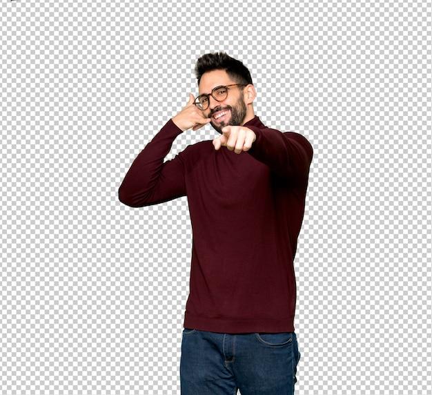 Homem bonito com óculos fazendo gesto de telefone e apontando a frente