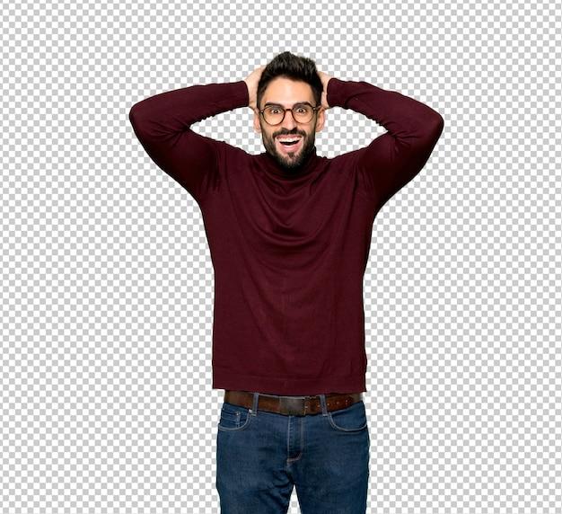 Homem bonito com óculos leva as mãos na cabeça porque tem enxaqueca