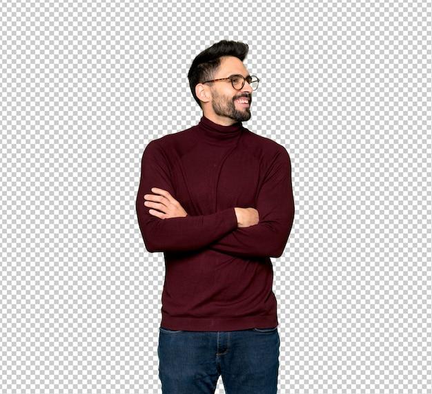 Homem bonito com óculos, mantendo os braços cruzados enquanto sorrindo
