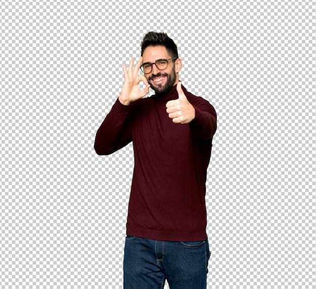 Homem bonito com óculos mostrando sinal de ok com e dando um polegar para cima gesto