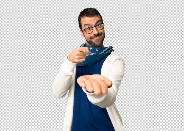 Homem bonito com óculos segurando copyspace imaginário na palma da mão para inserir um anúncio