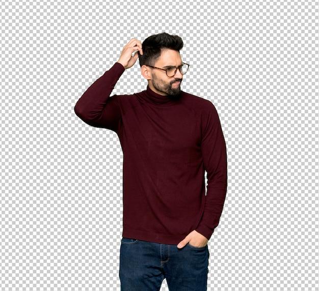 Homem bonito com óculos tendo dúvidas enquanto coçando a cabeça