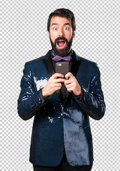 Homem bonito com paletó de lantejoulas falando ao celular