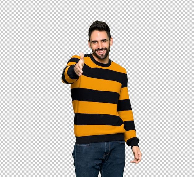 Homem bonito com suéter listrado, apertando as mãos para fechar um bom negócio