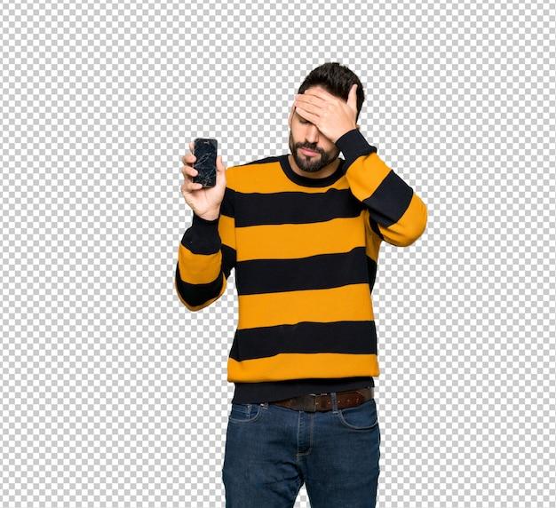 Homem bonito com suéter listrado com exploração perturbada smartphone quebrado