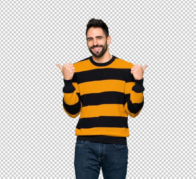 Homem bonito com suéter listrado, dando um polegar para cima gesto com as duas mãos e sorrindo