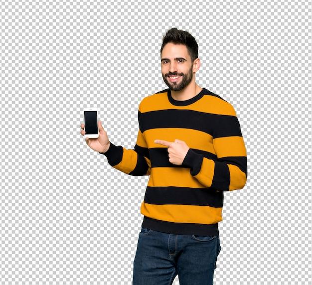 Homem bonito com suéter listrado feliz e apontando o celular