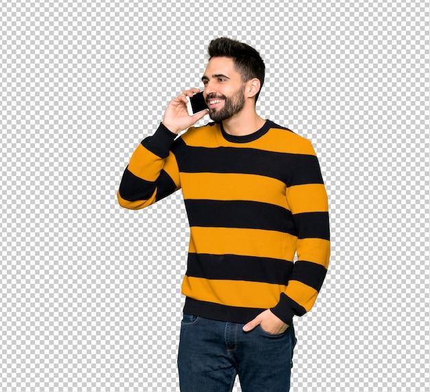 Homem bonito com suéter listrado, mantendo uma conversa com o telefone móvel