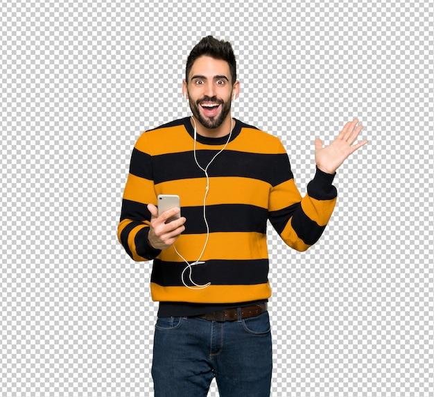 Homem bonito com suéter listrado surpreso e enviando uma mensagem