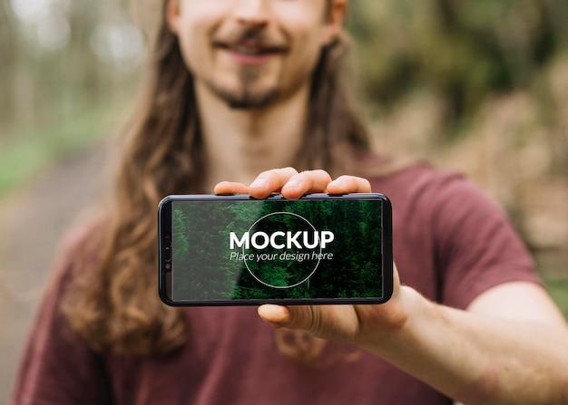 Homem bonito na natureza com maquete de smartphone