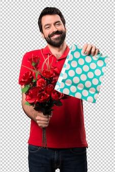 Homem bonito segurando flores com sacola de compras