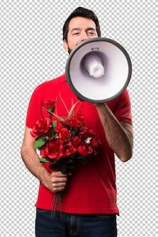 Homem bonito segurando flores segurando um megafone