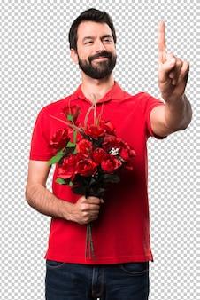 Homem bonito segurando flores tocando na tela transparente