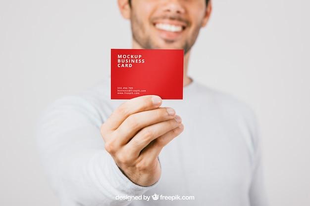 Homem borrado com cartão de visita em primeiro plano