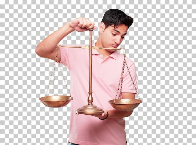 Homem bronzeado bonito jovem com um equilíbrio de justiça ou escala