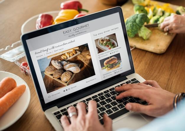 Homem caucasiano, usando um laptop na cozinha à procura de receitas