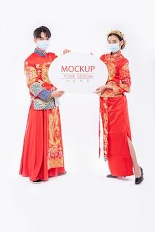 Homem chinês e mulher chinesa segurando um balão de fala em branco