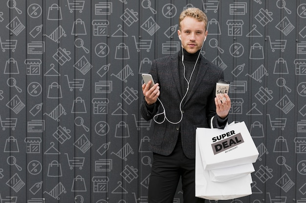 Homem com as mãos cheias de sacolas de compras
