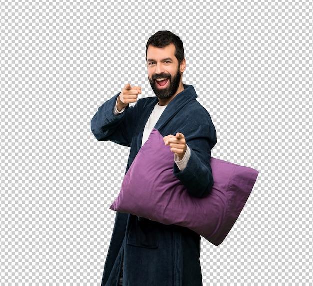 Homem com barba de pijama aponta o dedo para você enquanto sorrindo